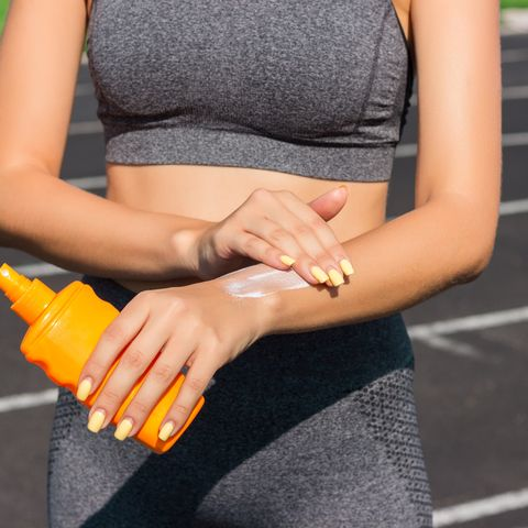 midsection of young athlete applying suntan lotion while standing on sports track
