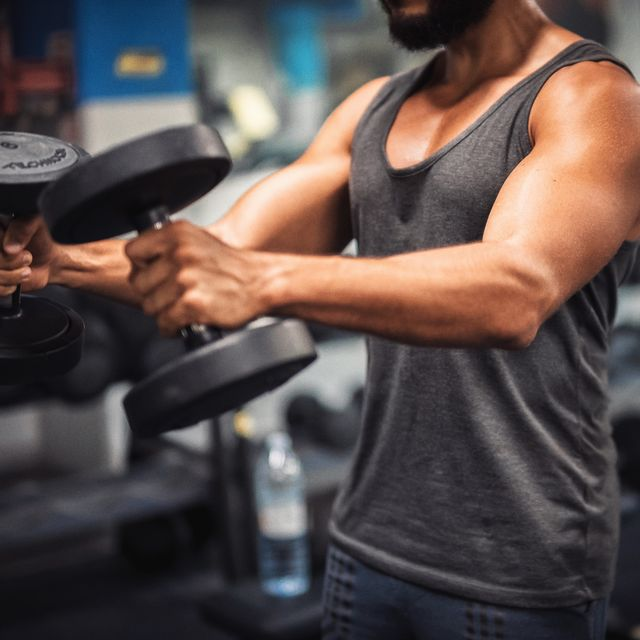 midsection of young man lifting dumbbell in gym