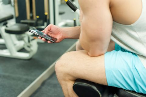 Midsection Of Young Man Using Phone While Sitting At Gym