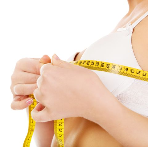 midsection of young woman measuring breasts against white background