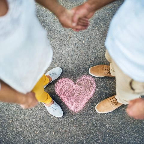 A midsection view of senior couple standing on a road, with chalk heart by their feet.