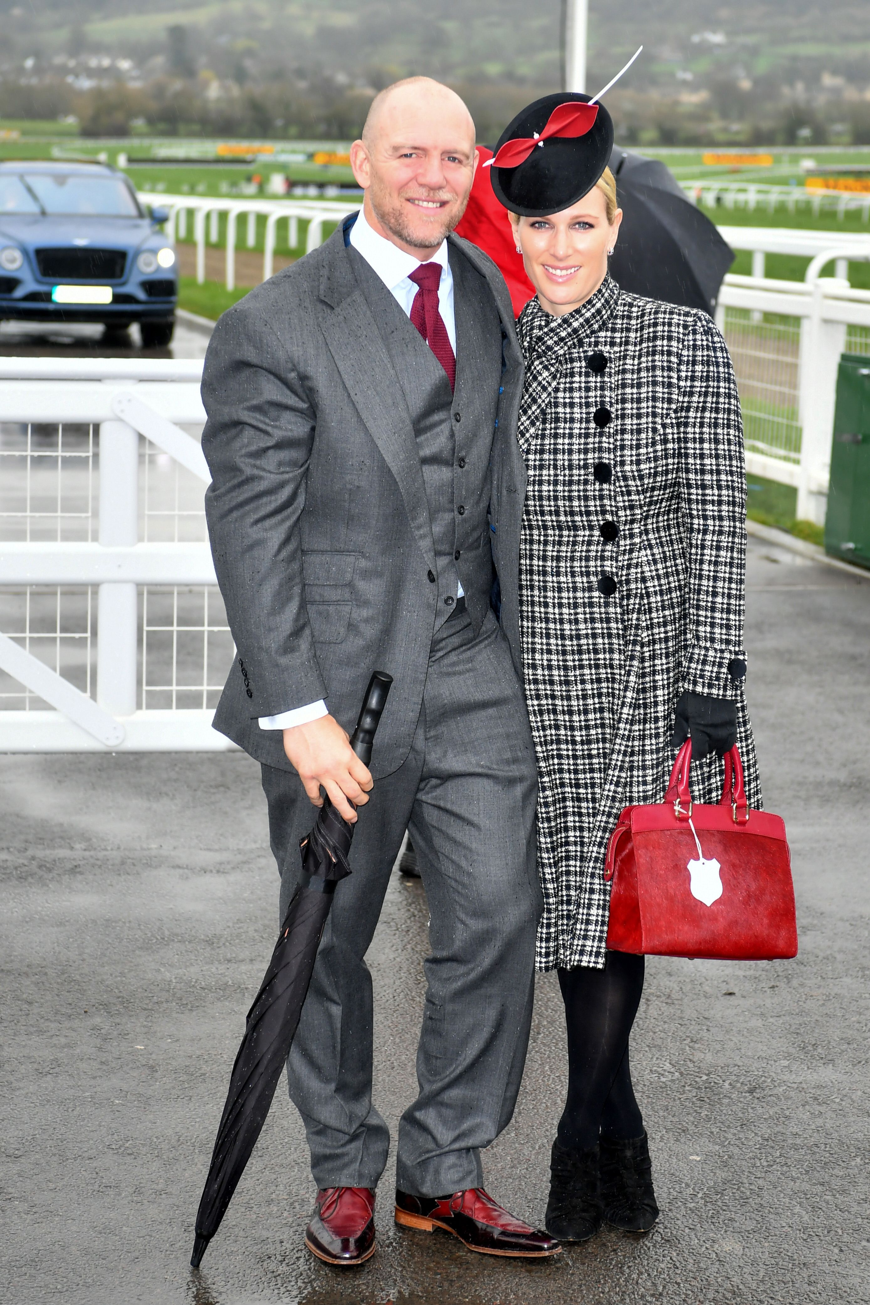 Mike and Zara Tindall attended Gold Cup Day at the Cheltenham races. Zara paired a black and white plaid coat with a red top handle bag, black booties and a black hat featuring a large red bow.