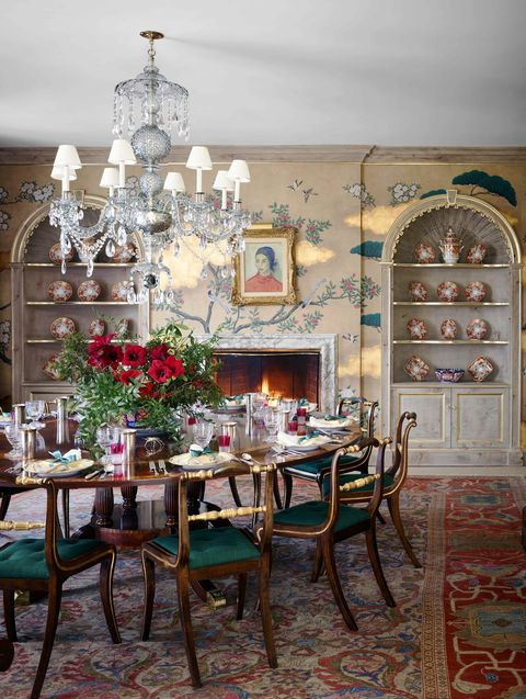 a round dining table with chairs all around and a crystal chandelier above