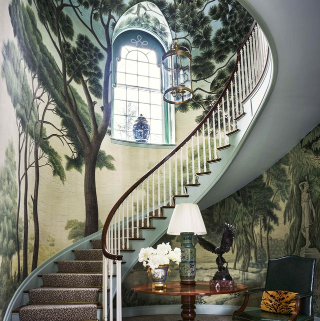 a winding staircase with a forest mural