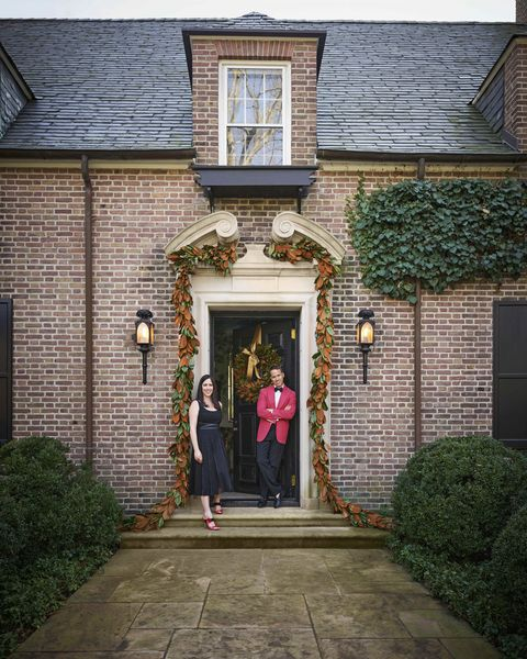 the brick exterior of a connecticut house with a man and woman standing at the front door