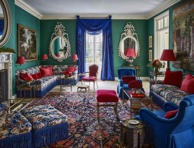 a living room with green walls and floral furniture and blue curtains with red accents all over