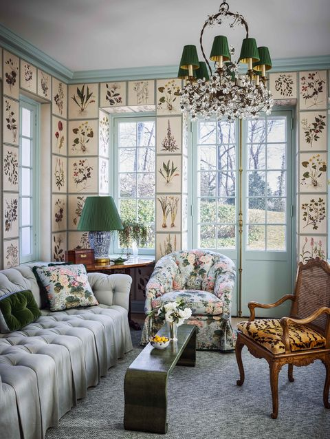 walls in the office are lined with botanical drawings and has a soafa and two chairs and a chandelier