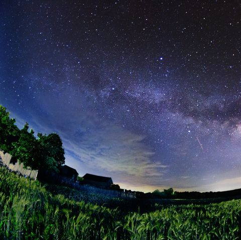 milky way star galaxy night shot near a contryside house in a wheat field