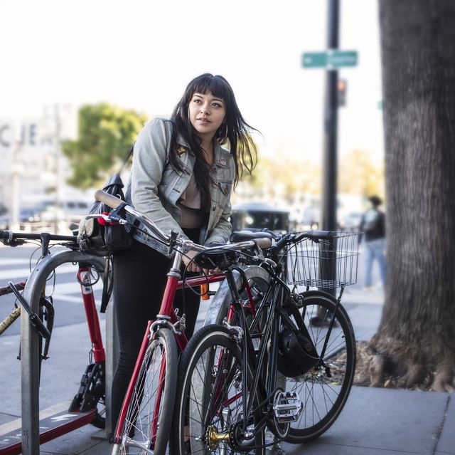 millennial latina bicycle commuting, locking her bike on city sidewalk