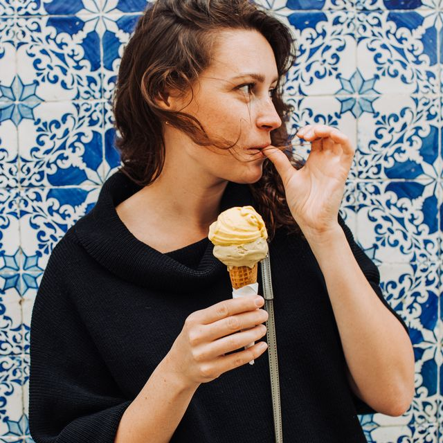 millennial woman licking finger while eating ice cream at a tiled wall