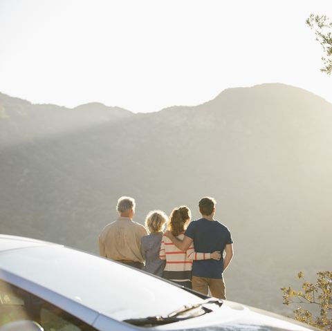 Family looking at mountain view outside car