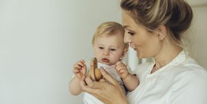 Mother showing her baby a wooden toy