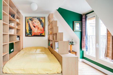 Pequeño dormitorio con estanterías de madera a cada lado