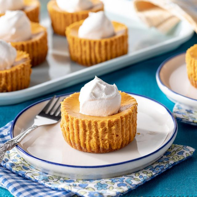 mini pumpkin cheesecakes on a small white plate with a fork and flower linen with a tray of mini cheesecakes in the background