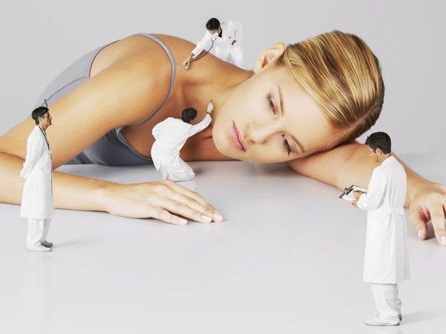 Miniature doctors examining a woman