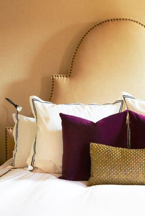 beige bedroom with pink velvet pillows