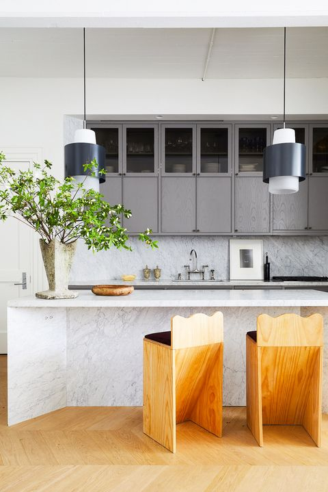 modern kitchen with marble island and wooden stools