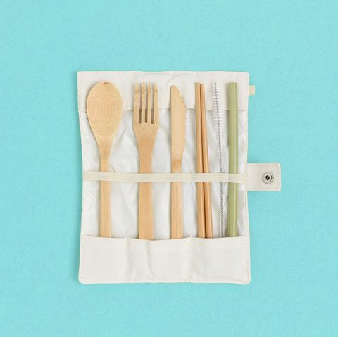 set of bamboo cutlery in a case on a green pastel background zero waste concept