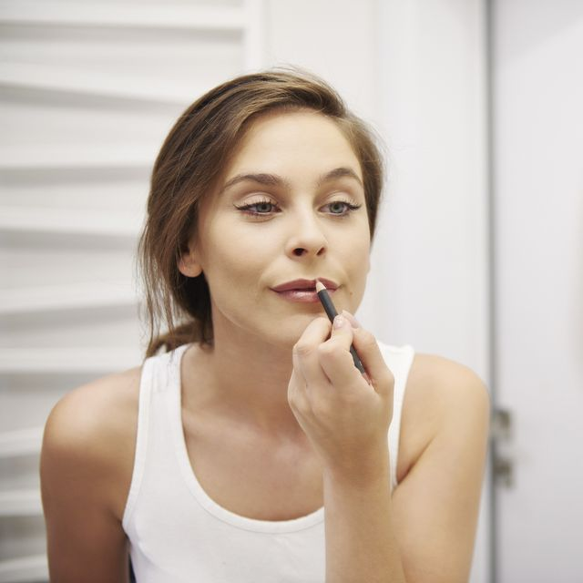 mirror image of young woman in bathroom applying lipliner