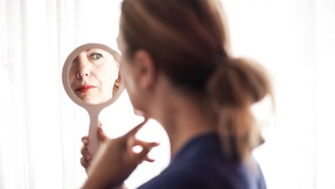 Mirror reflection of mature woman