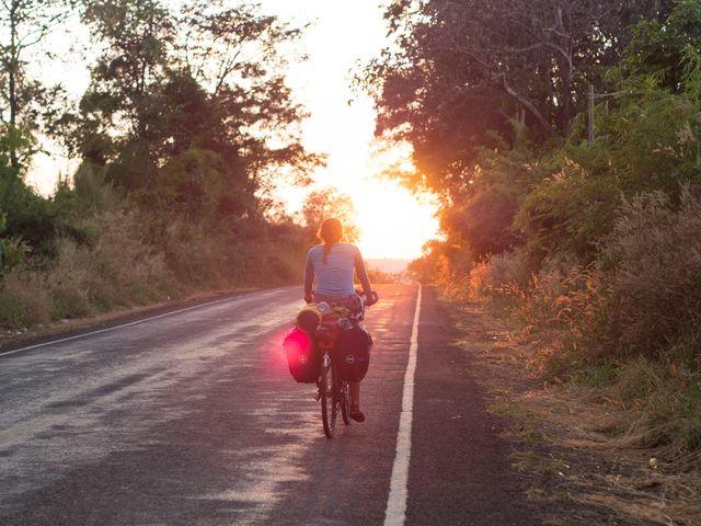 vrouw fietst met bepakking over asfaltweg richting ondergaande zon