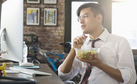 Mixed Race businessman using computer and eating salad at desk