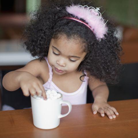 mixed race girl drinking hot chocolate