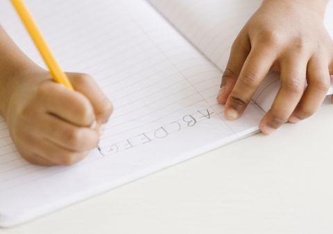 Mixed race girl writing ABC's