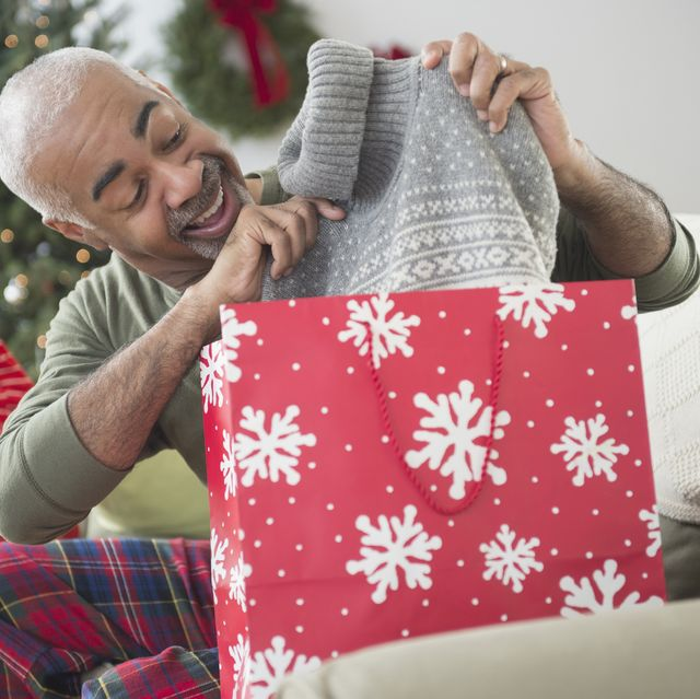mixed race grandfather and grandson opening christmas gifts