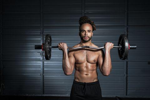 Mixed Race man lifting weights in gymnasium
