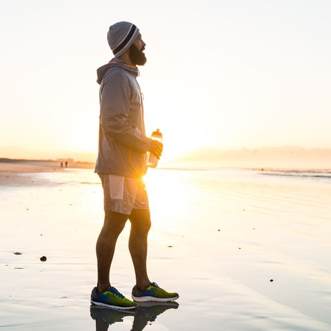 Mixed race man running on the beach at dawn