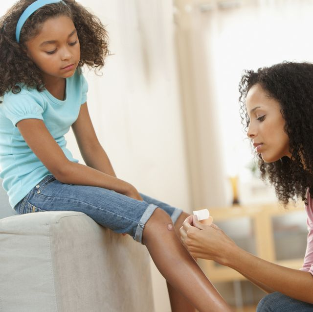 Mixed race mother putting bandage on daughter