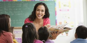 Mixed race teacher reading to students