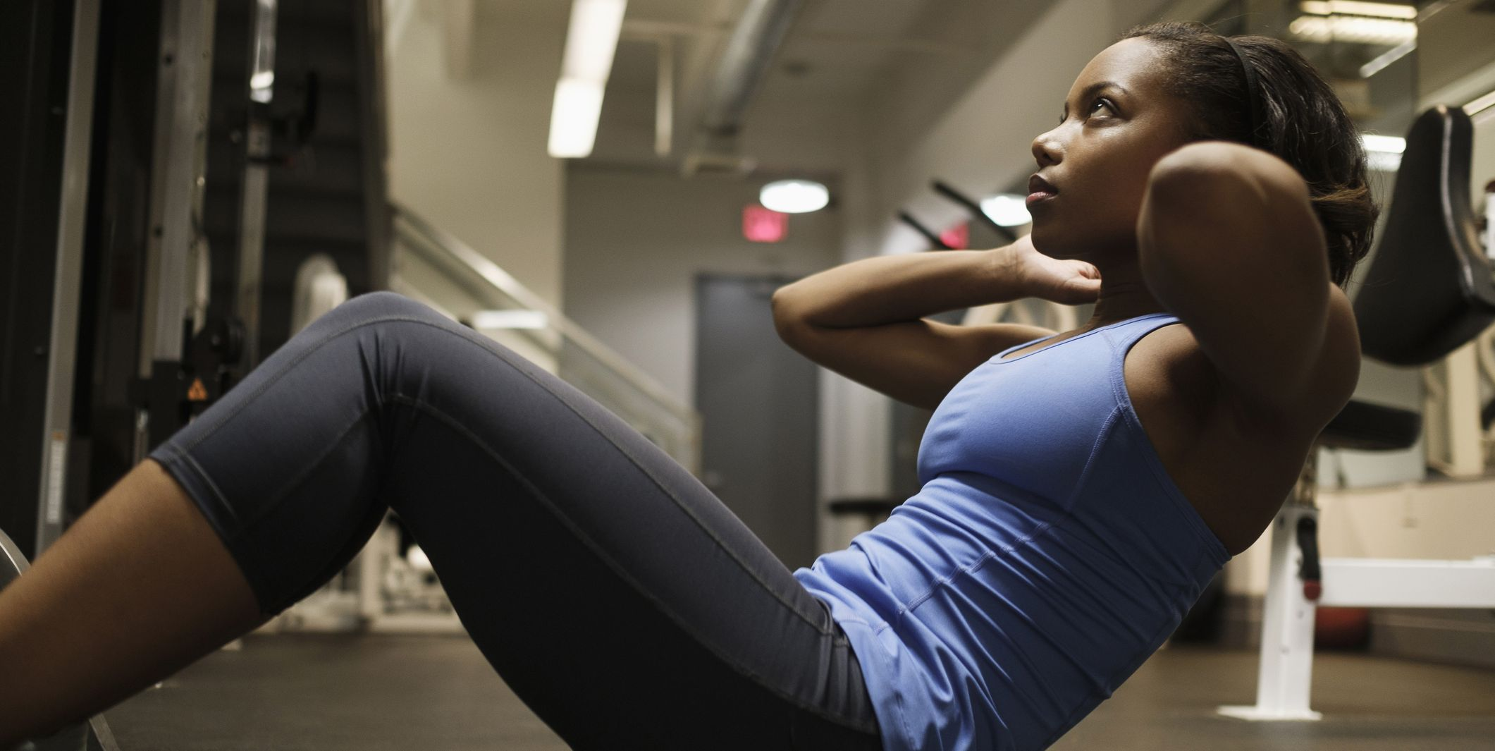 Mixed Race woman doing sit-up on floor at gymnasium