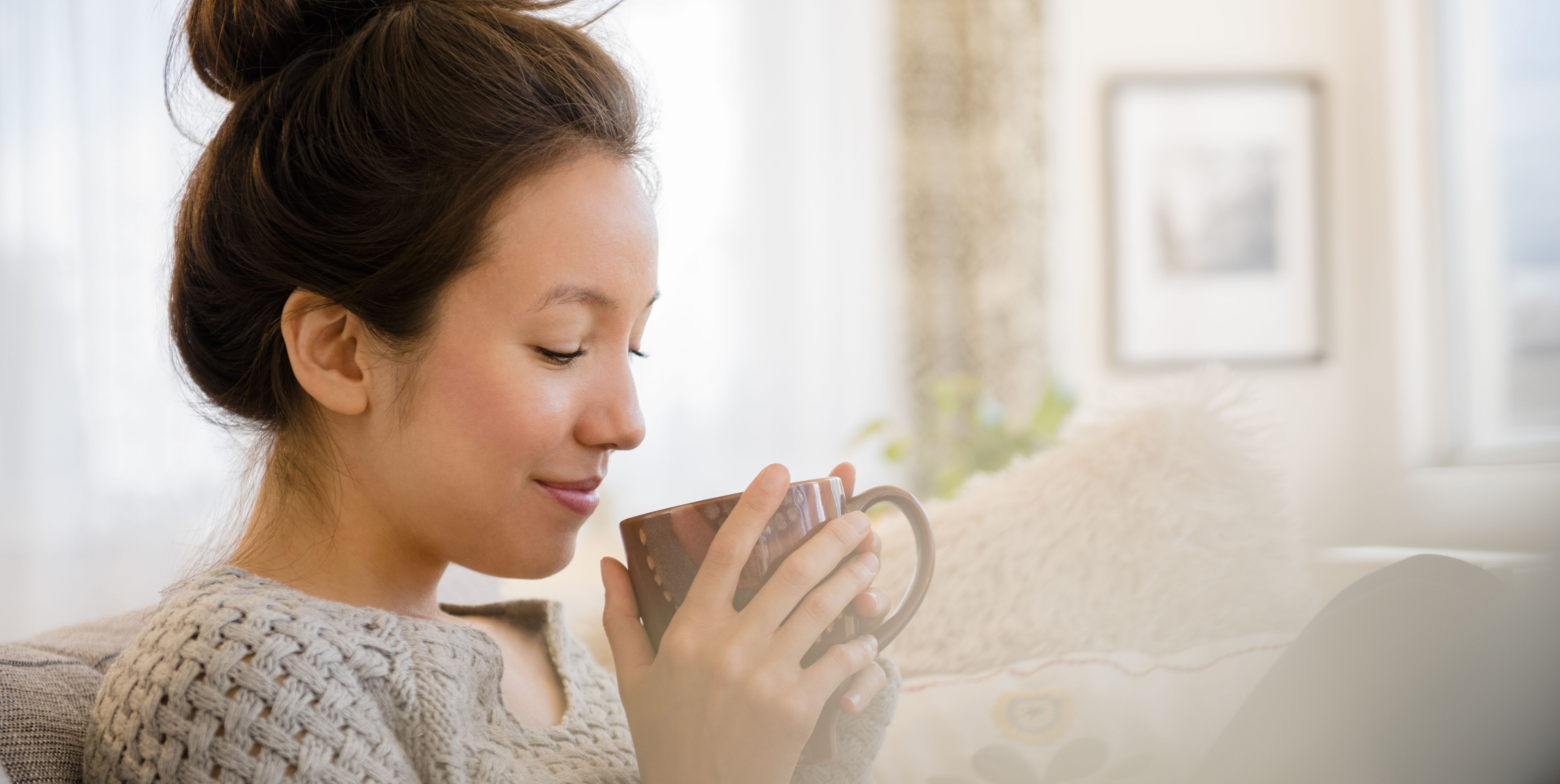 Mixed race woman drinking coffee on sofa