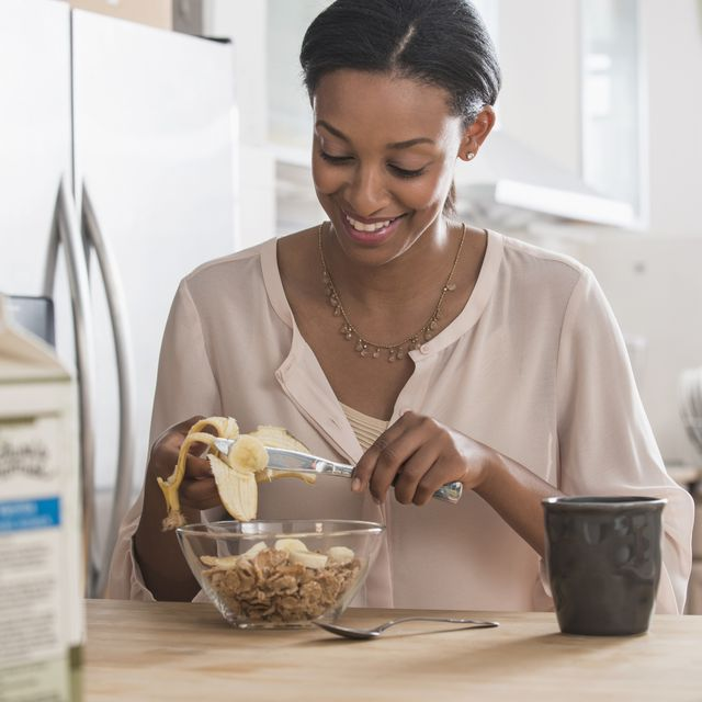 mixed race woman eating cereal and banana in kitchen