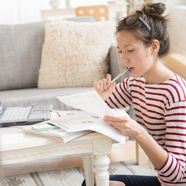 Mixed race woman paying bills on laptop