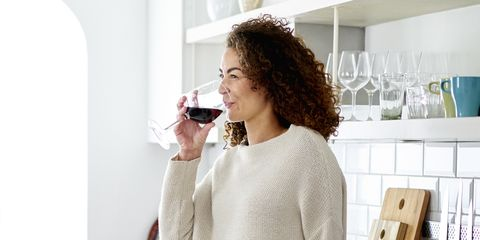 mixed race woman relaxing drinking red wine at home in kitchen
