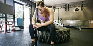 Mixed Race woman resting on tire holding sledgehammer in gymnasium