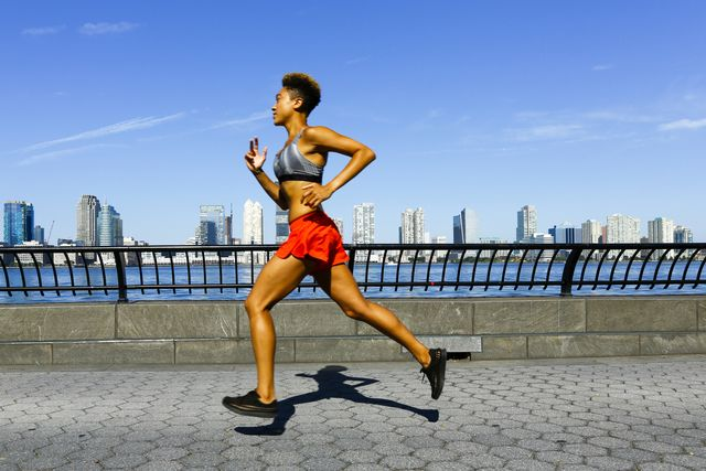 mixed race woman running at waterfront