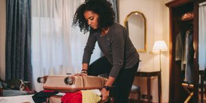 Mixed race woman struggling with overflowing suitcase before journey