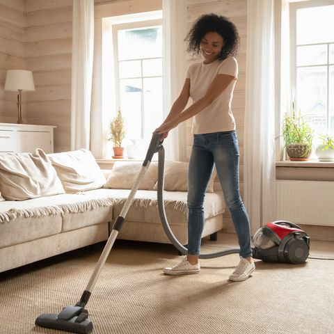 mixed race woman vacuum cleaning carpet in living room