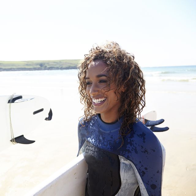 mixed race woman with surfboard walking on the be