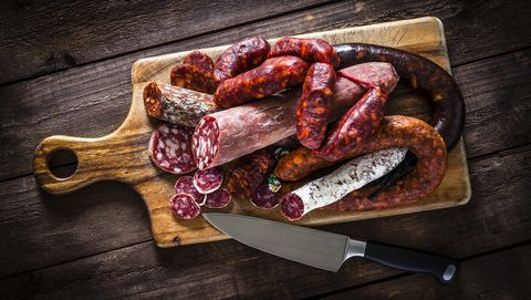 Mixed spanish chorizo pieces shot from above on rustic wooden table
