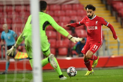 mo salah prepares to shoot for goal as he plays football for liverpool in a champions' league game