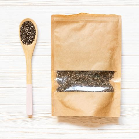 Mockup paper bag with Chia seeds and wooden spoon on white wooden table. Concept of a healthy diet. Super food.