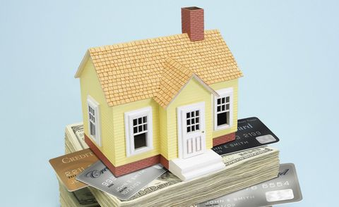 Model house on stack of US paper currency and credit cards