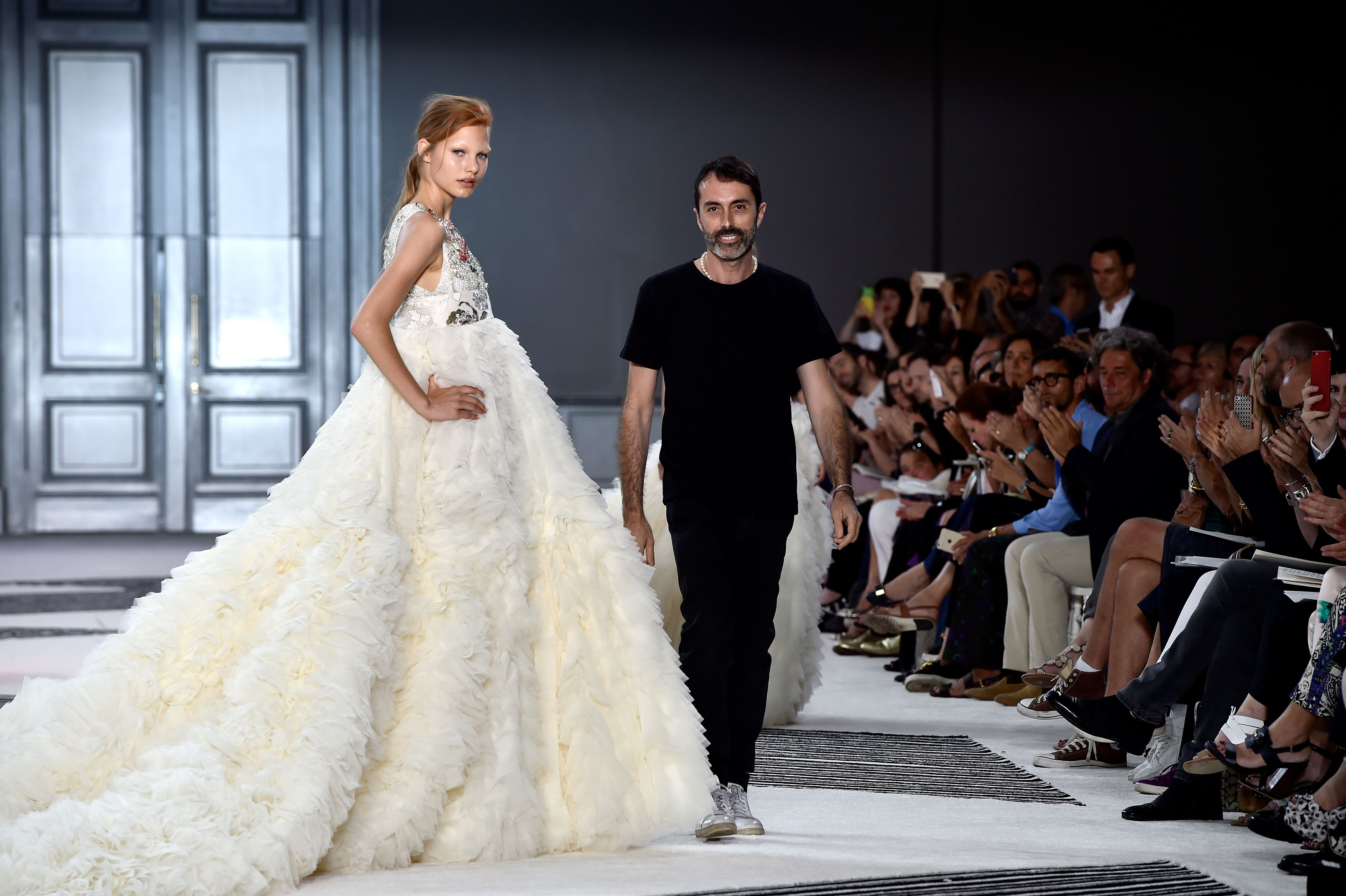 Valli takes a bow with a model after his Fall 2015 couture show in Paris in July 2015.