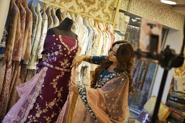 a model showcases a bridal dress to the customers via