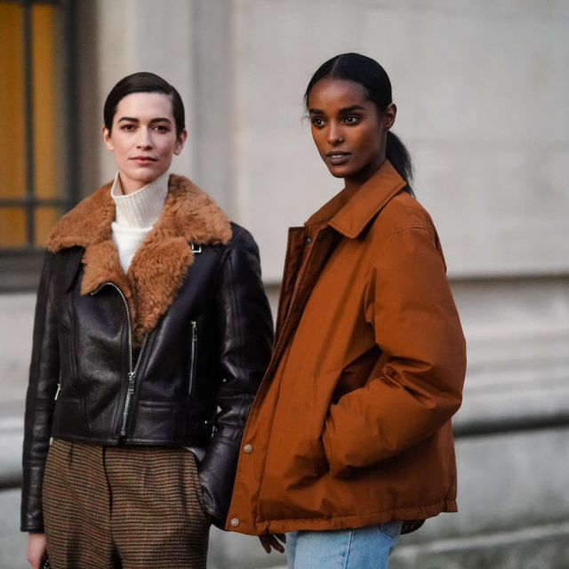 two models in fall jackets stand on a street corner in paris